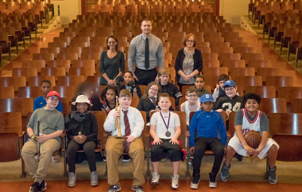 Group photo of 16 GW students, their teacher, and classroom aides who took part in Black History Month wax museum
