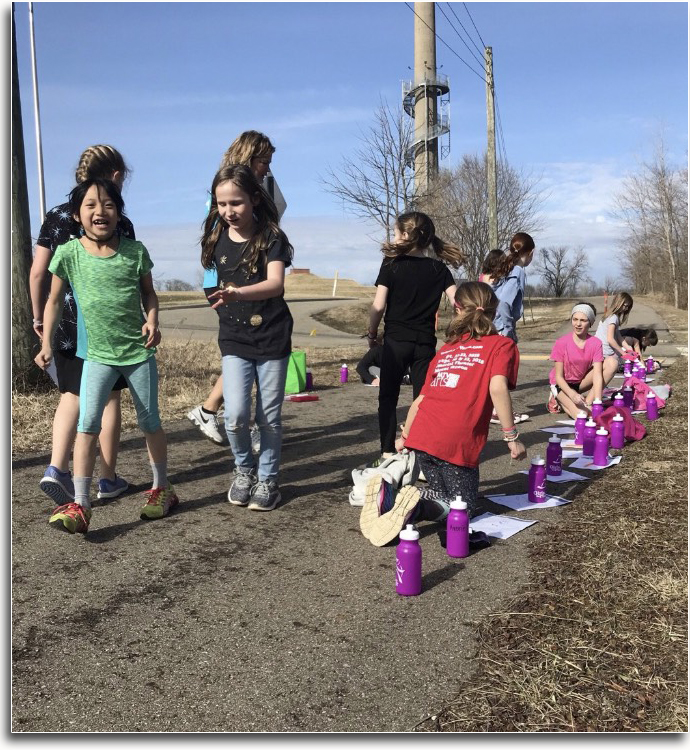Girls on the run on the bikepath with their water bottles.