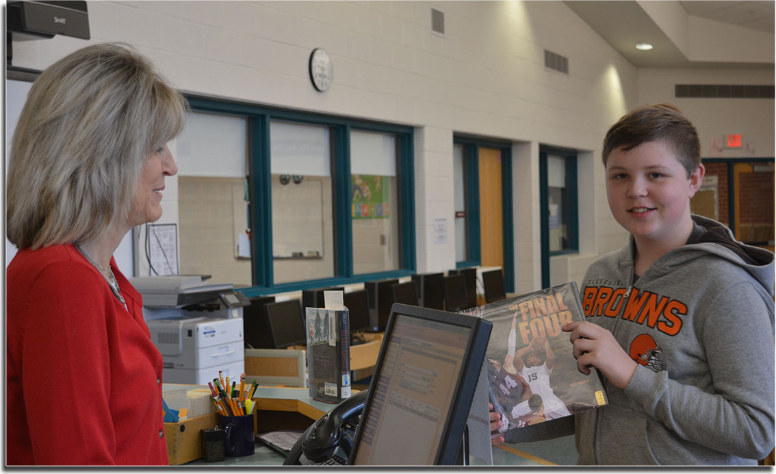 Student checking out book in the Middle School library.