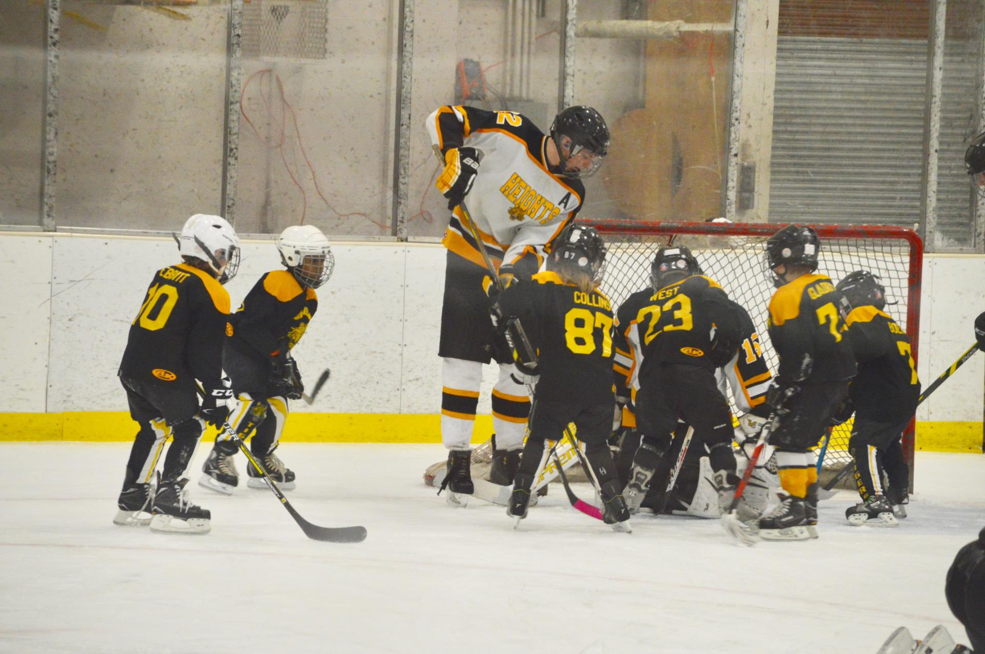 Heights player with Mites players on ice