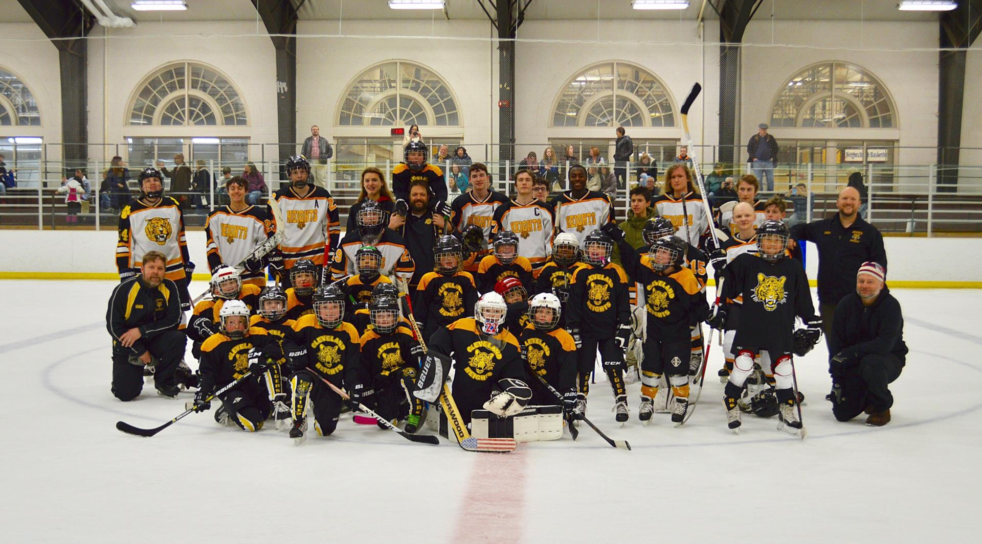 Group photo of Heights High hockey players and Mites players
