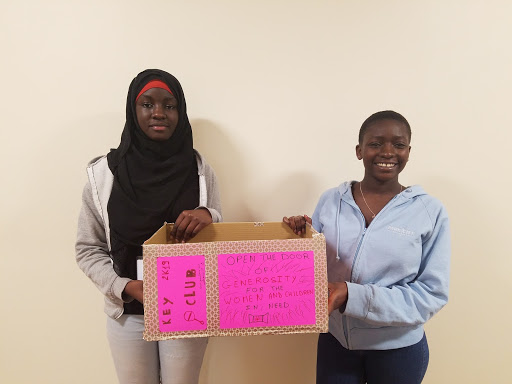 Two students holding a box for donations