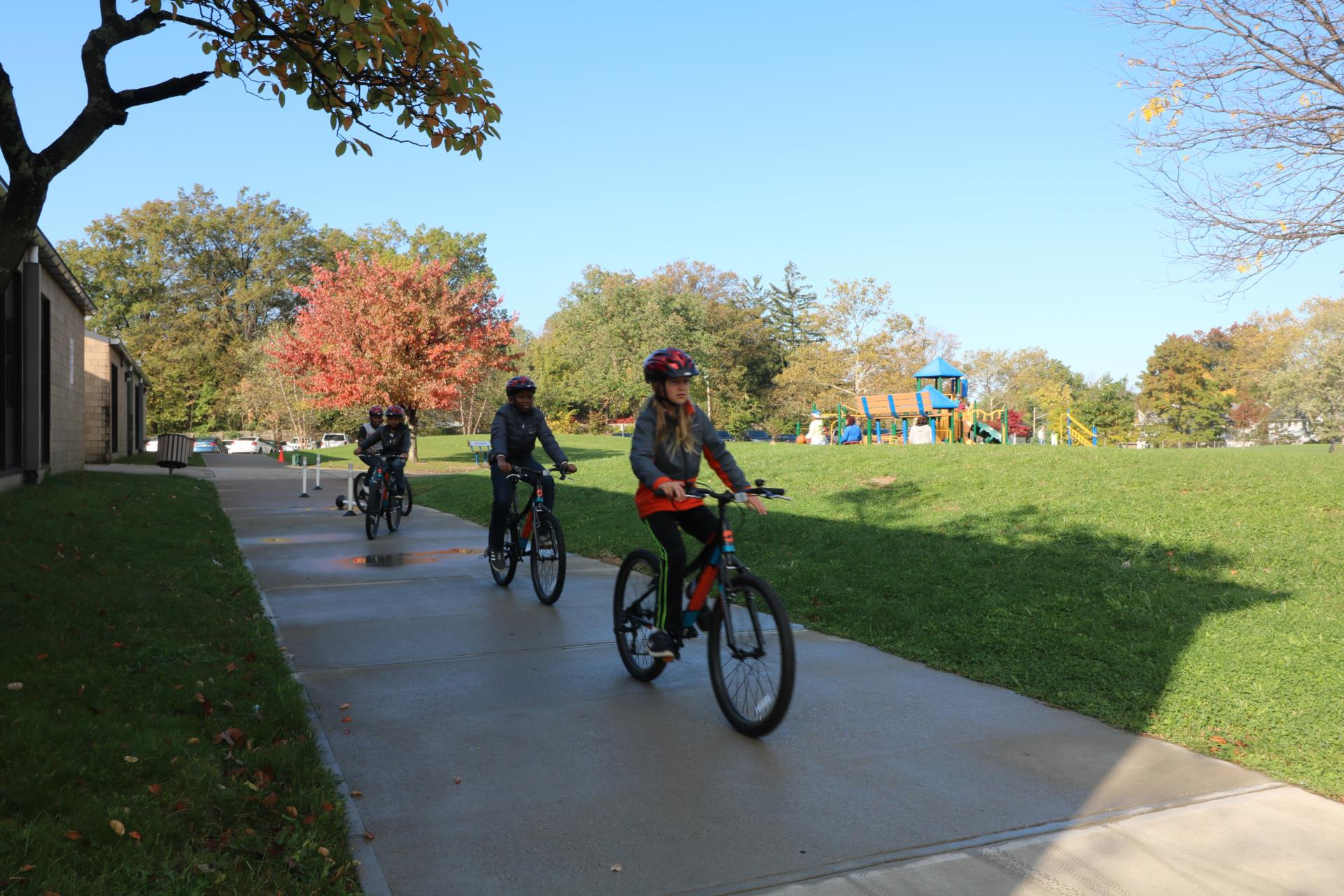 Students riding bikes on path