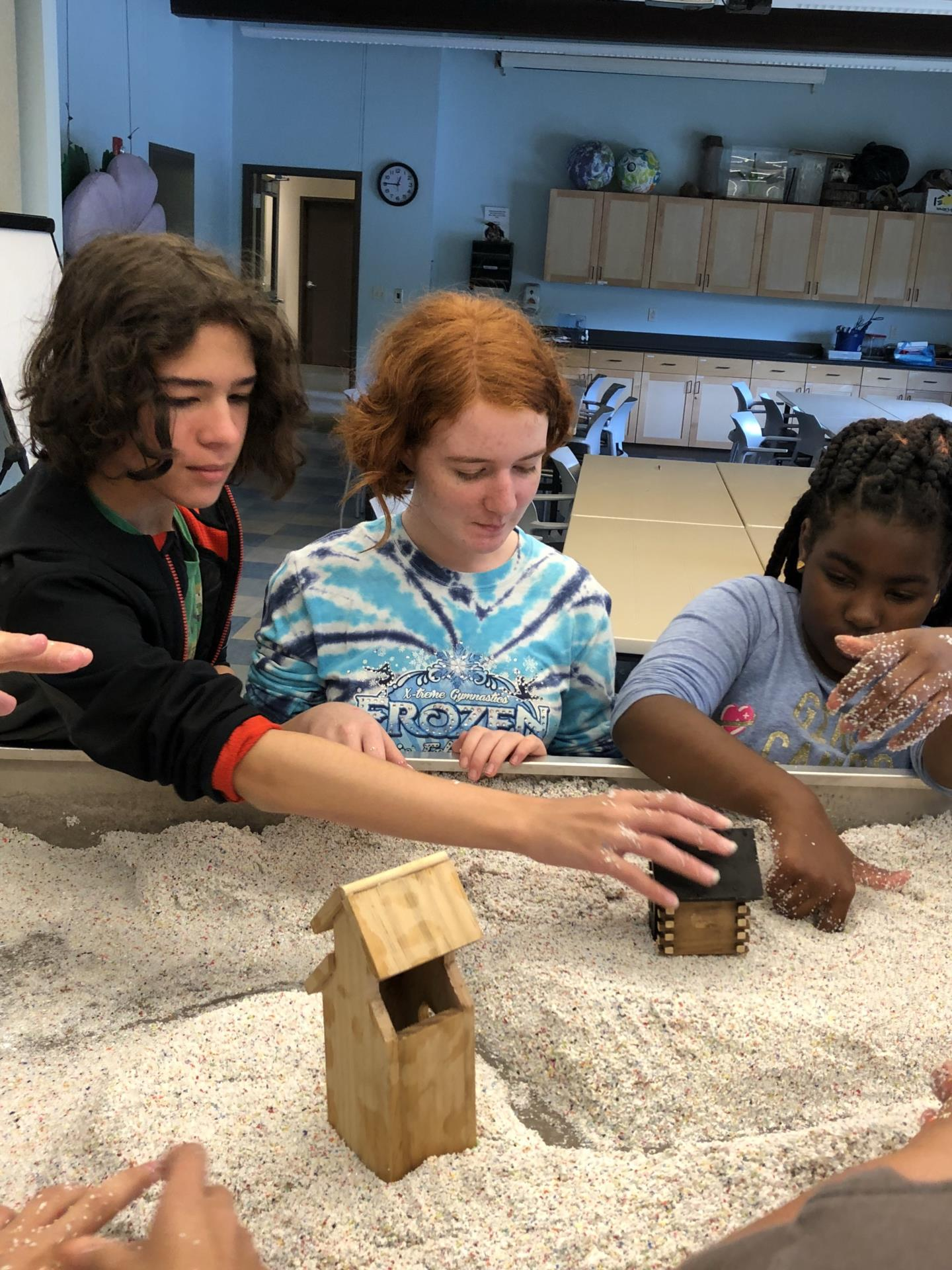 Three students working with sand in box