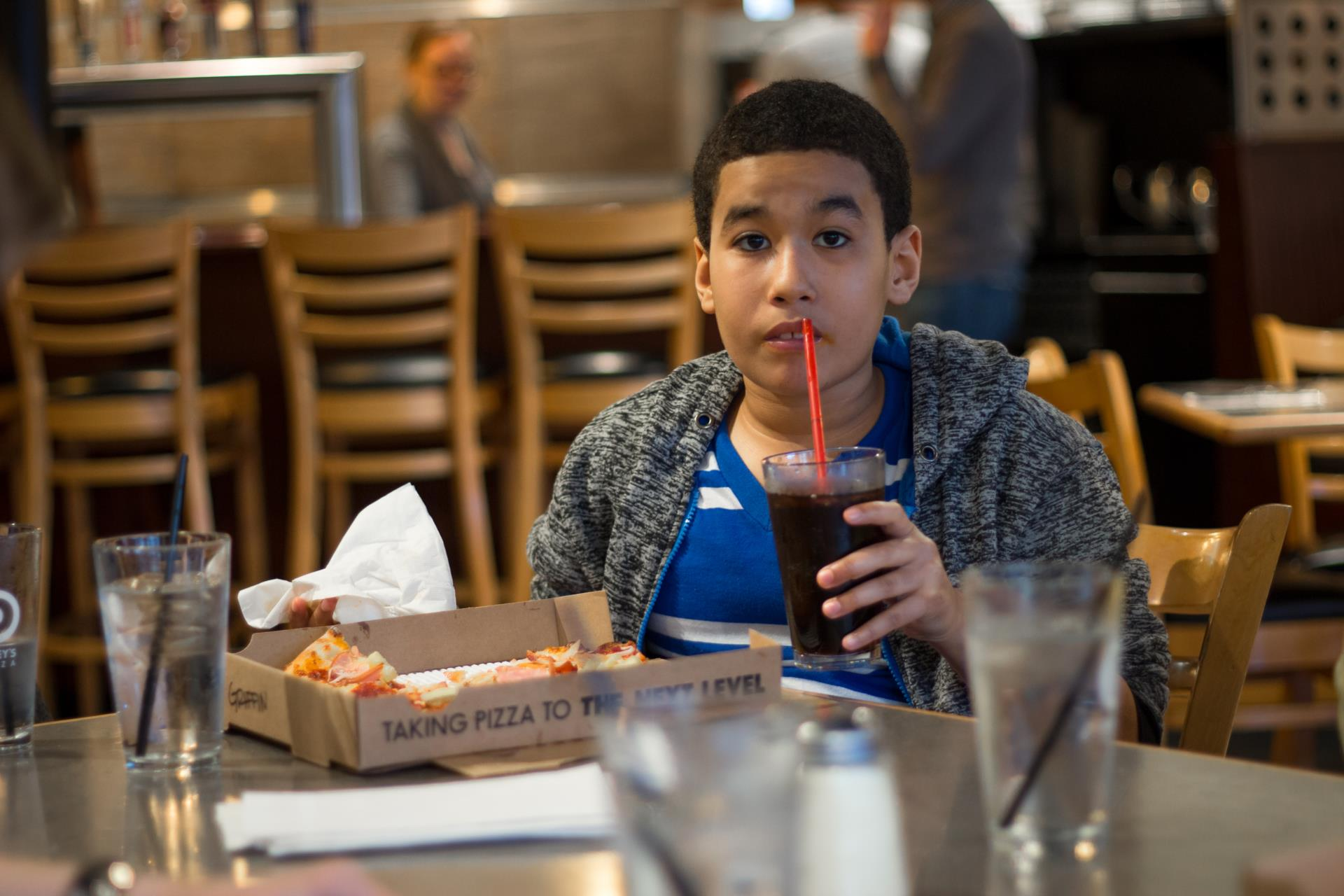 Boy drinking pop at table