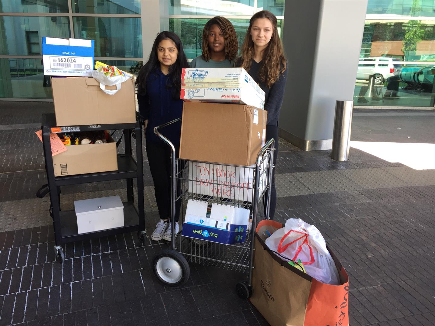 Three students with the donations they collected