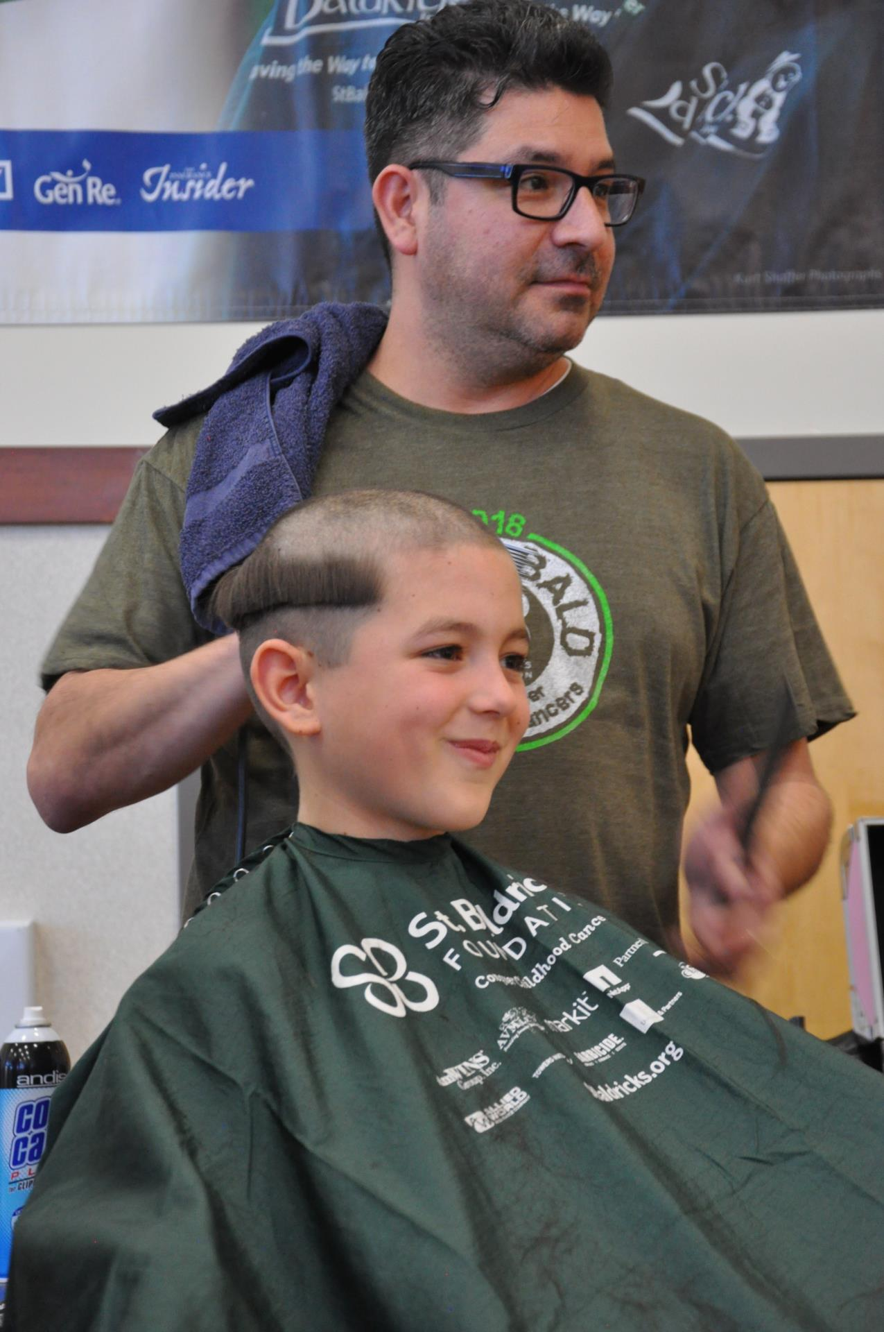 Barber Alex Quintana jokes with the parents of RoxEl 4th grader Jude West, mid-shave