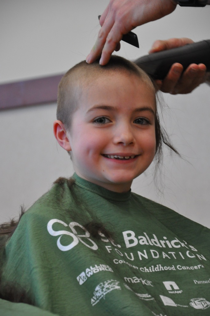 Young female smiling while getting head shaved