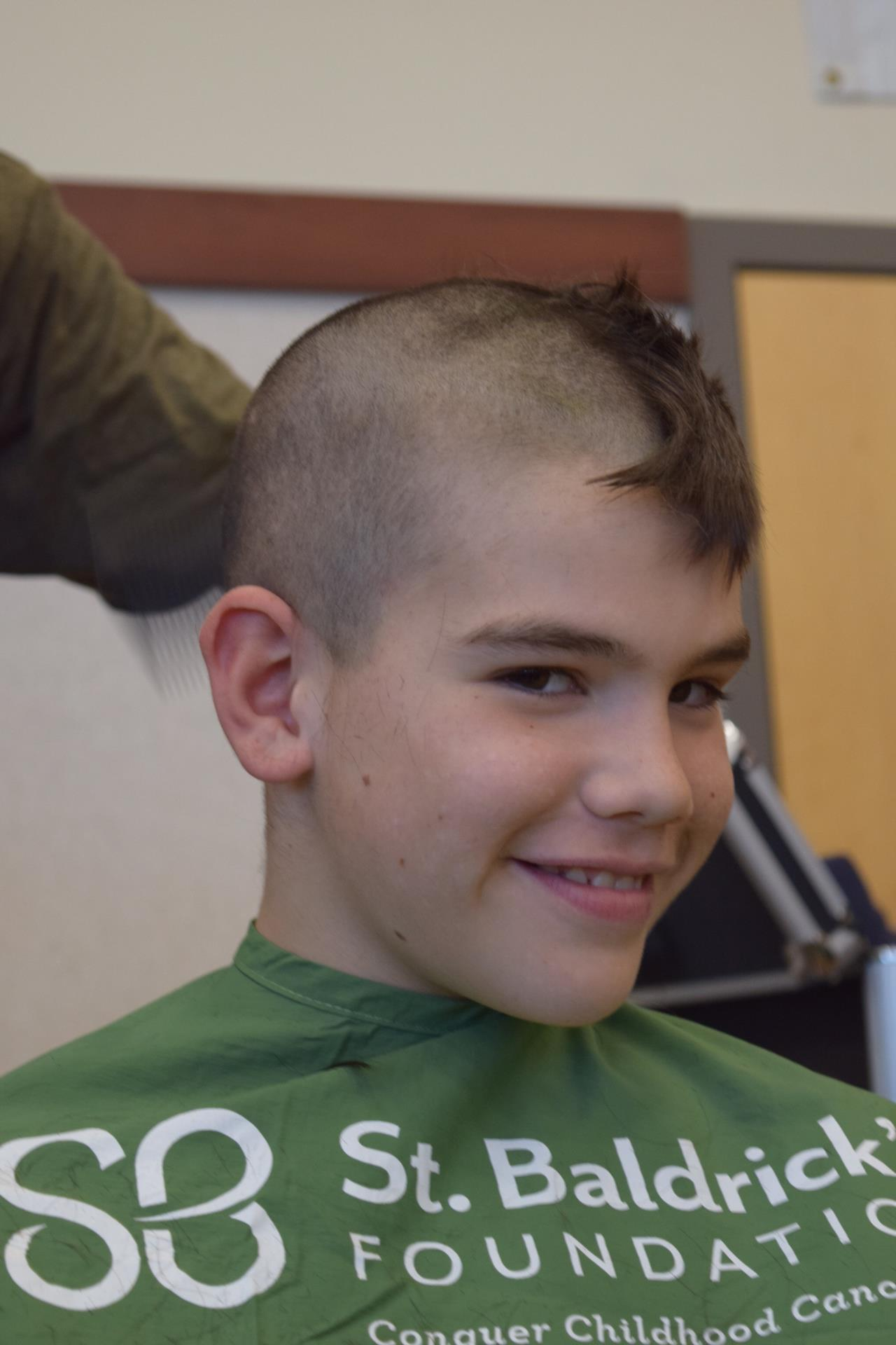 Male student smiling while getting head shaved
