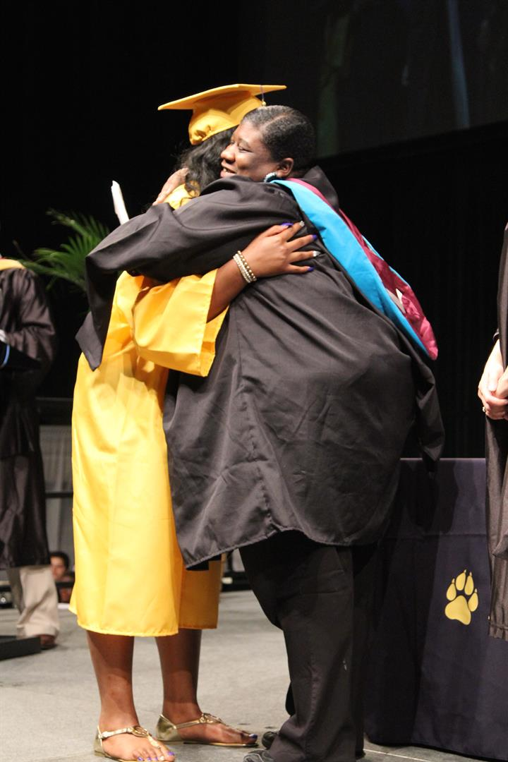 Board Member Tisha Thomas hugging graduating senior at 2016 commencement ceremony.