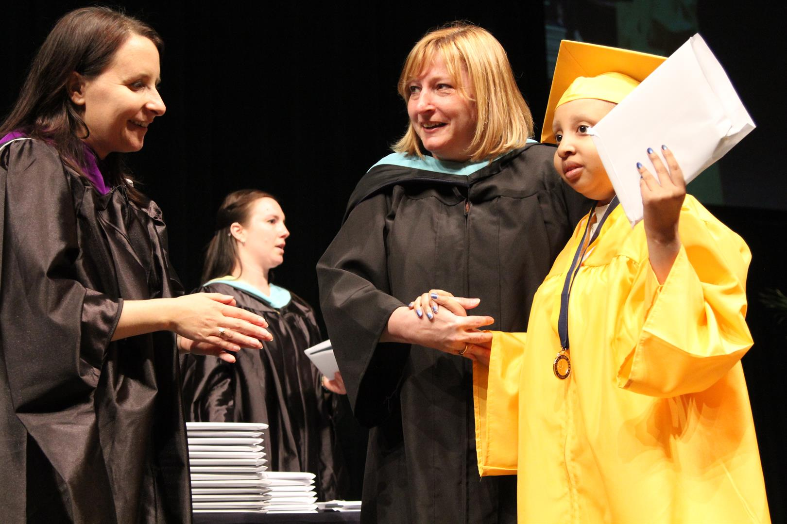 Kathy DeAngelis Board Member giving student a diploma