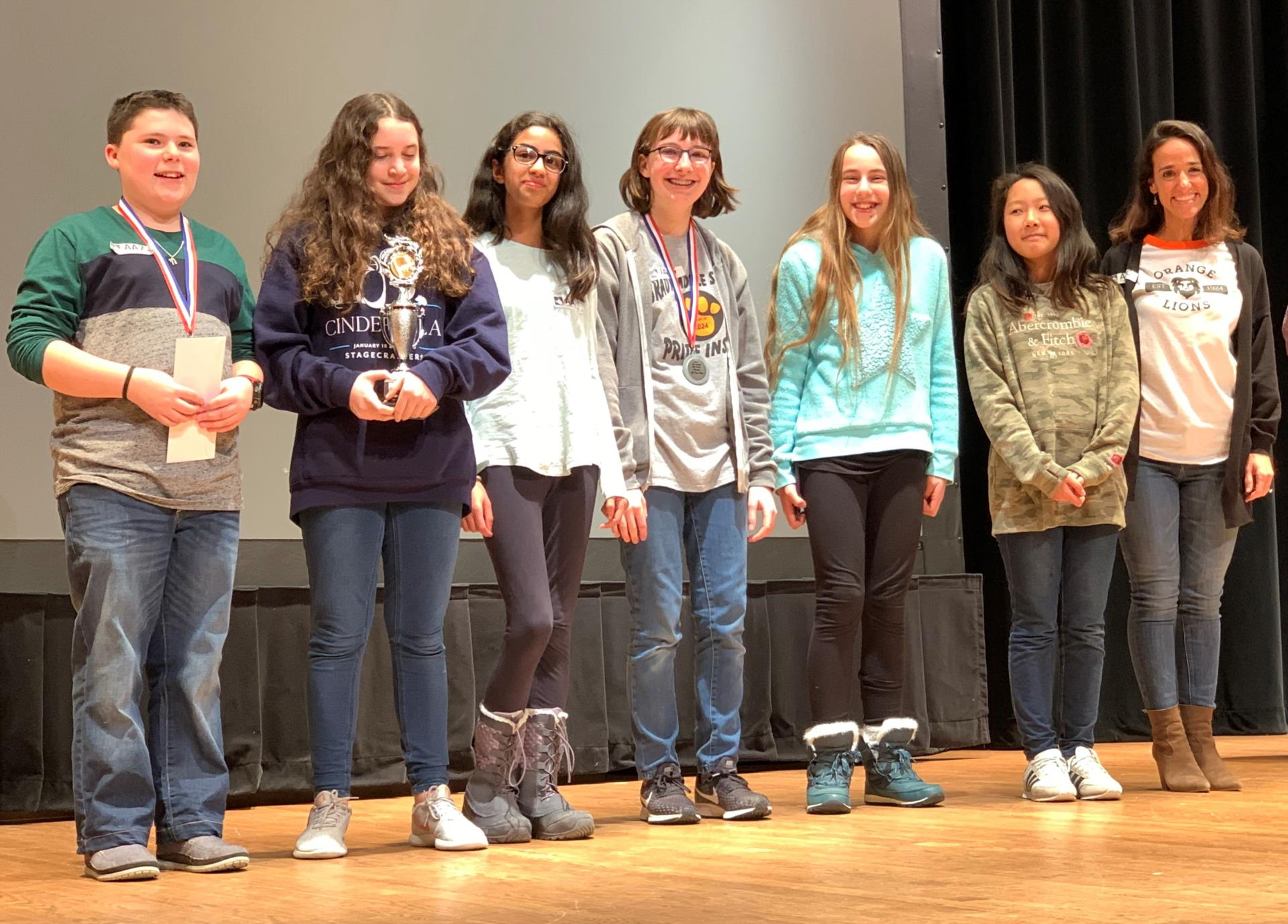 BMS seventh graders and their advisor line up on stage with trophy