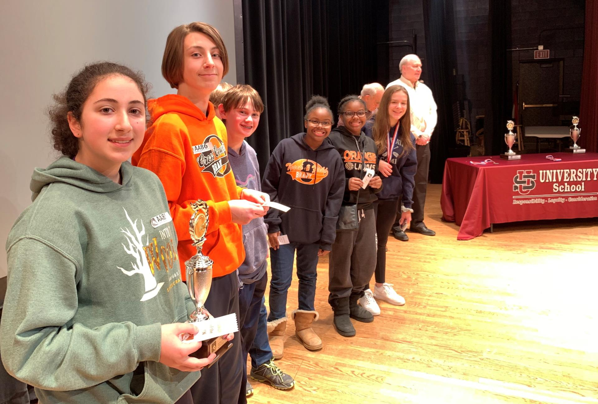 BMS eighth graders line up on stage with winning trophy