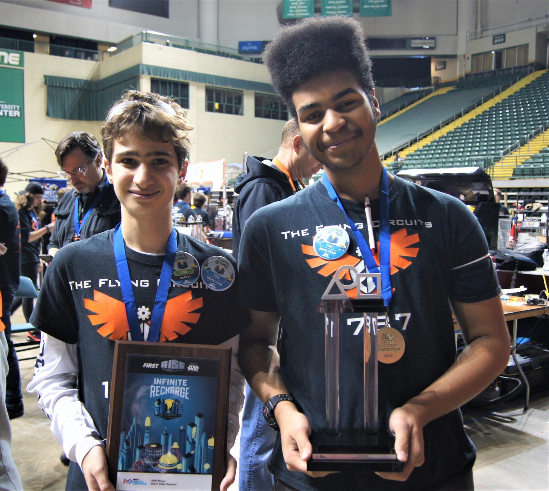 Two students hold Robotics Trophies