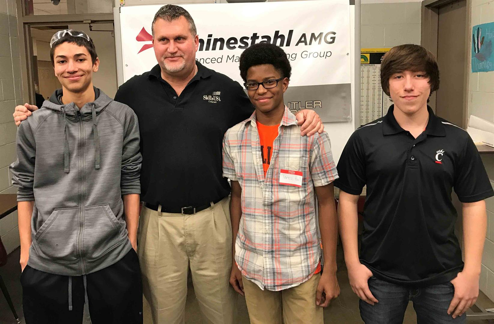 Three precision machining students and instructor