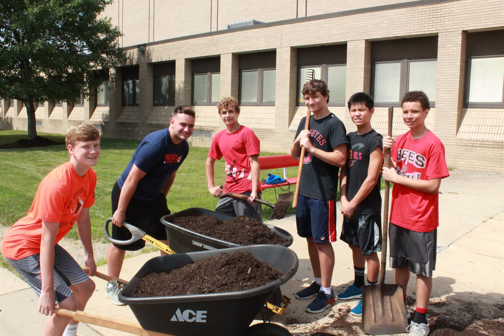 Varsity football players spreading mulch