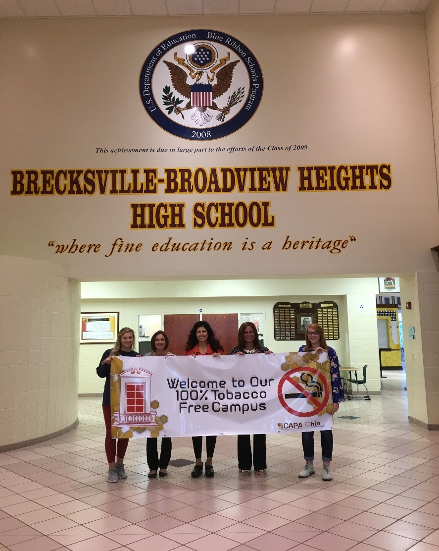 Students and staff with banner