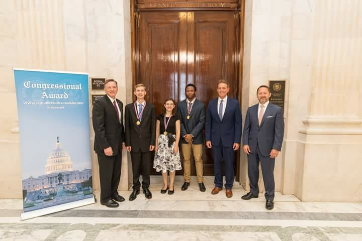 Student poses with Congressman for earning award