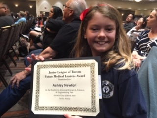 Elementary school student poses with science fair award