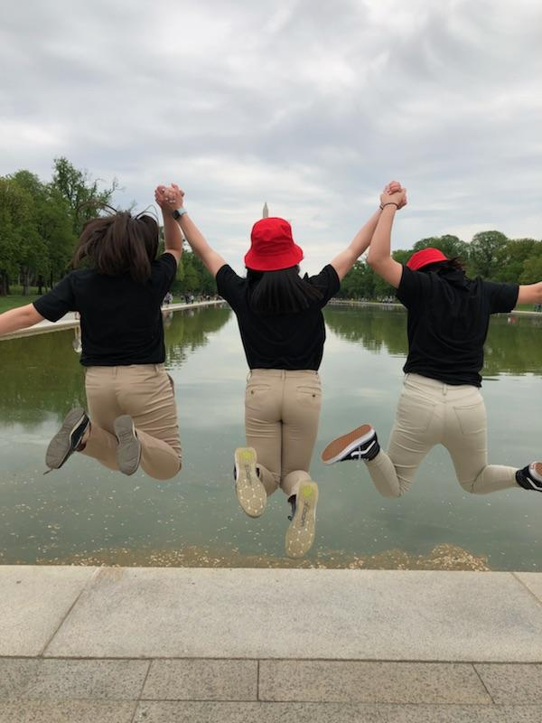 3 female JROCT cadets jumping in front of the reflection pool in front of the washington monument