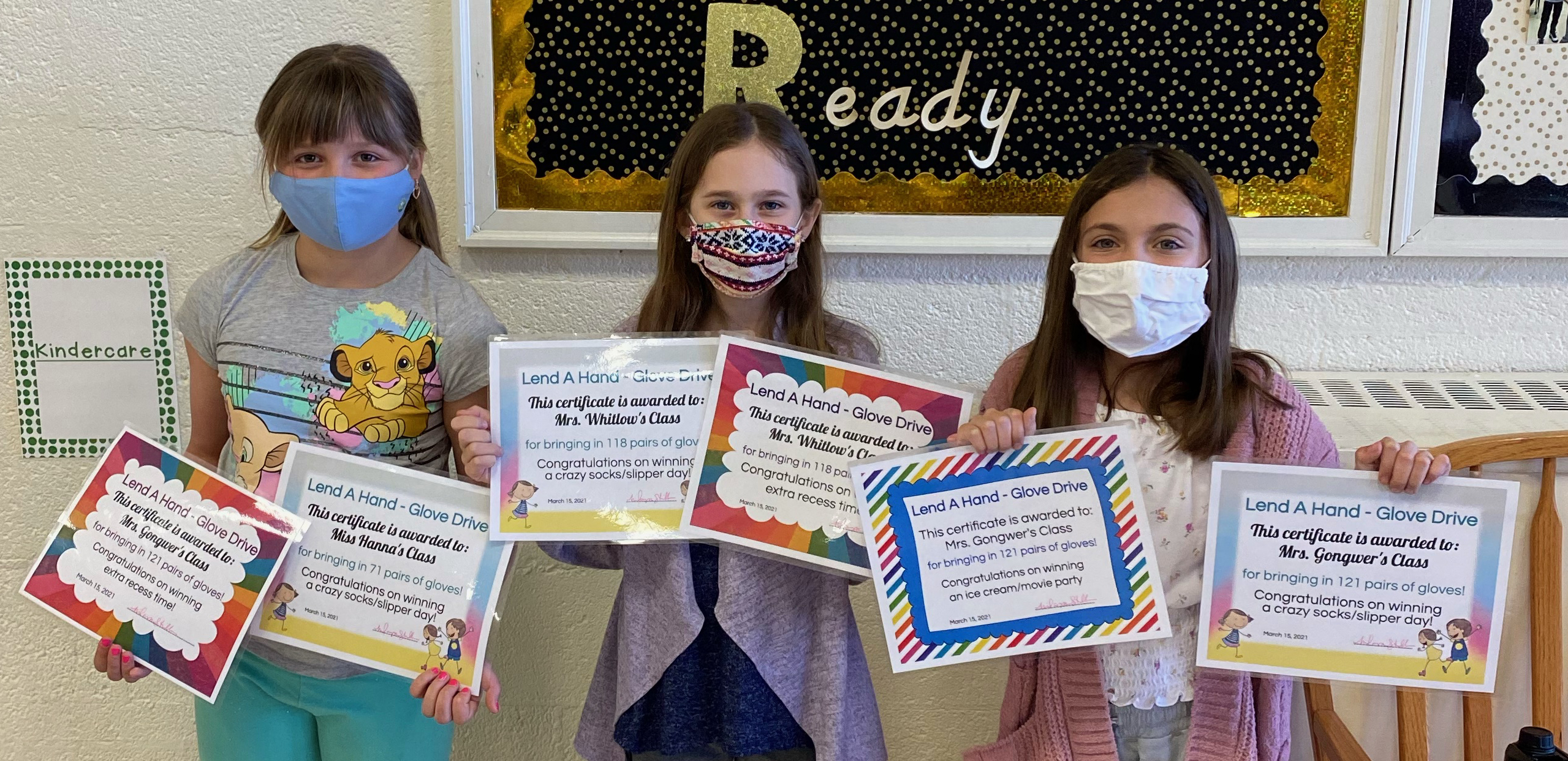 three students wearing masks and holding up certificates