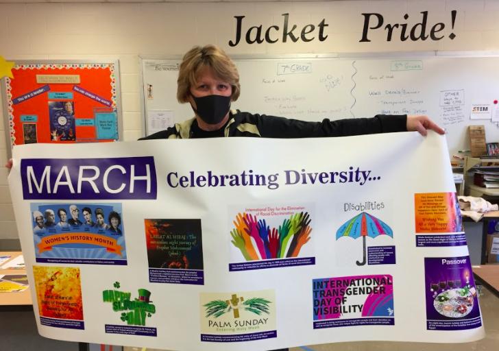 Adult holding March Celebrating Diversity poster