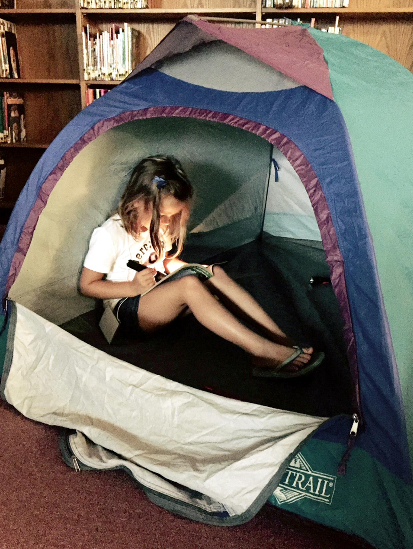 student reading in a tent