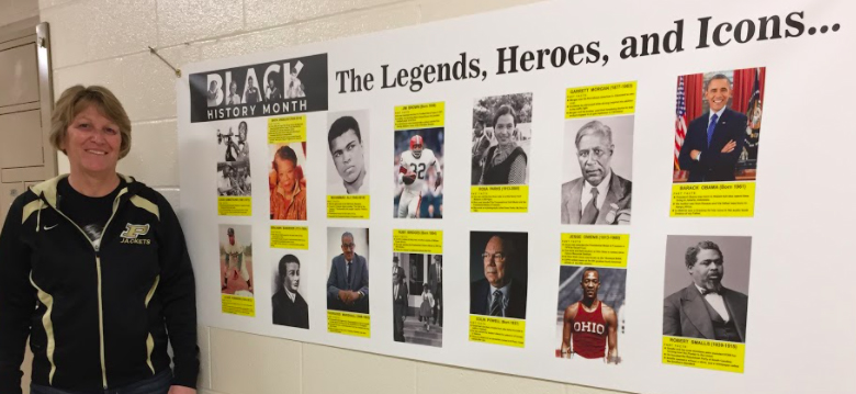 Adult standing next to Black History Month poster