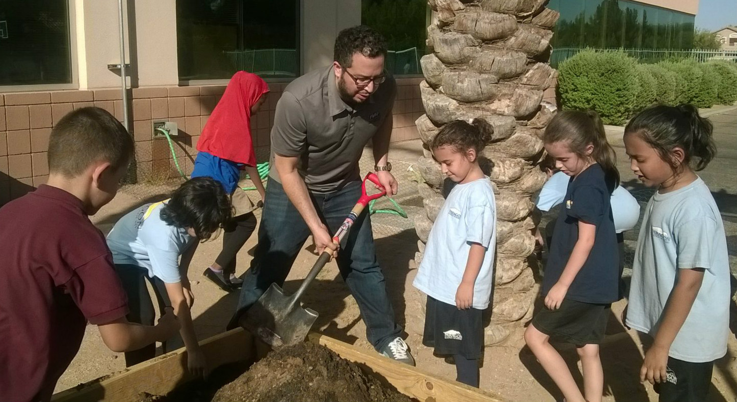 Parent and students working in a garden