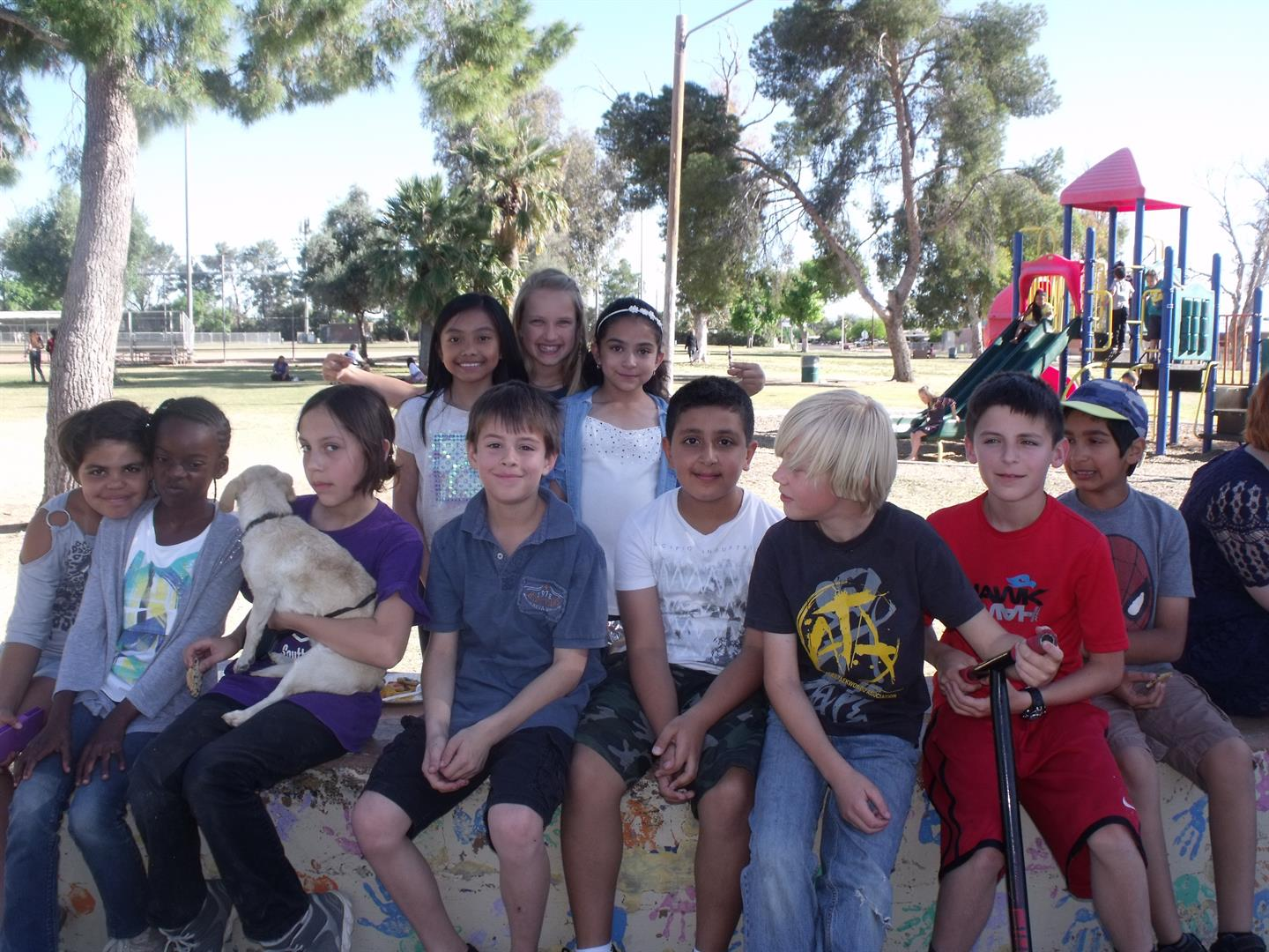 Children posing for a group photo at a playground