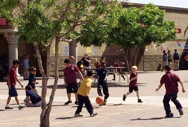 Children play soccer on our enclosed playground