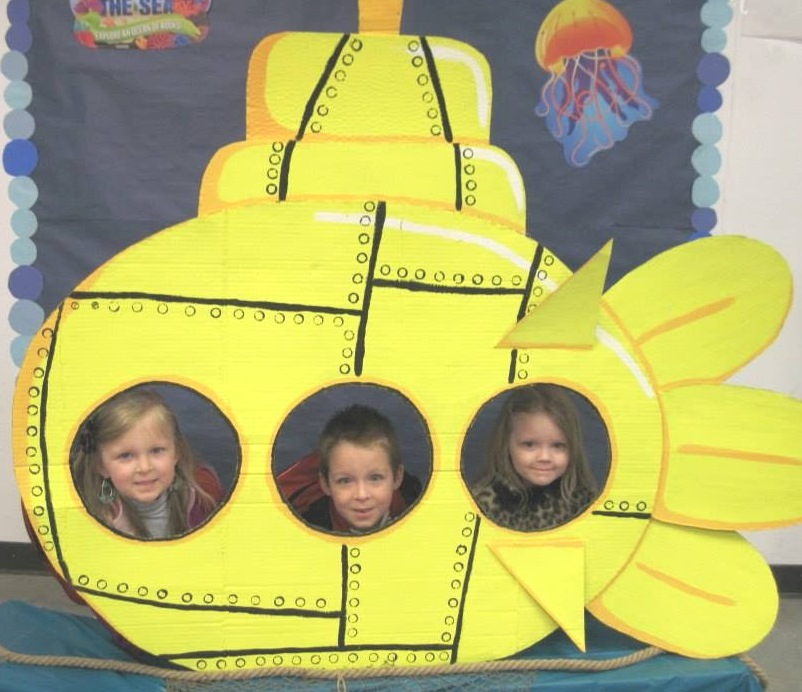 Three tots pose in a cutout of a submarine