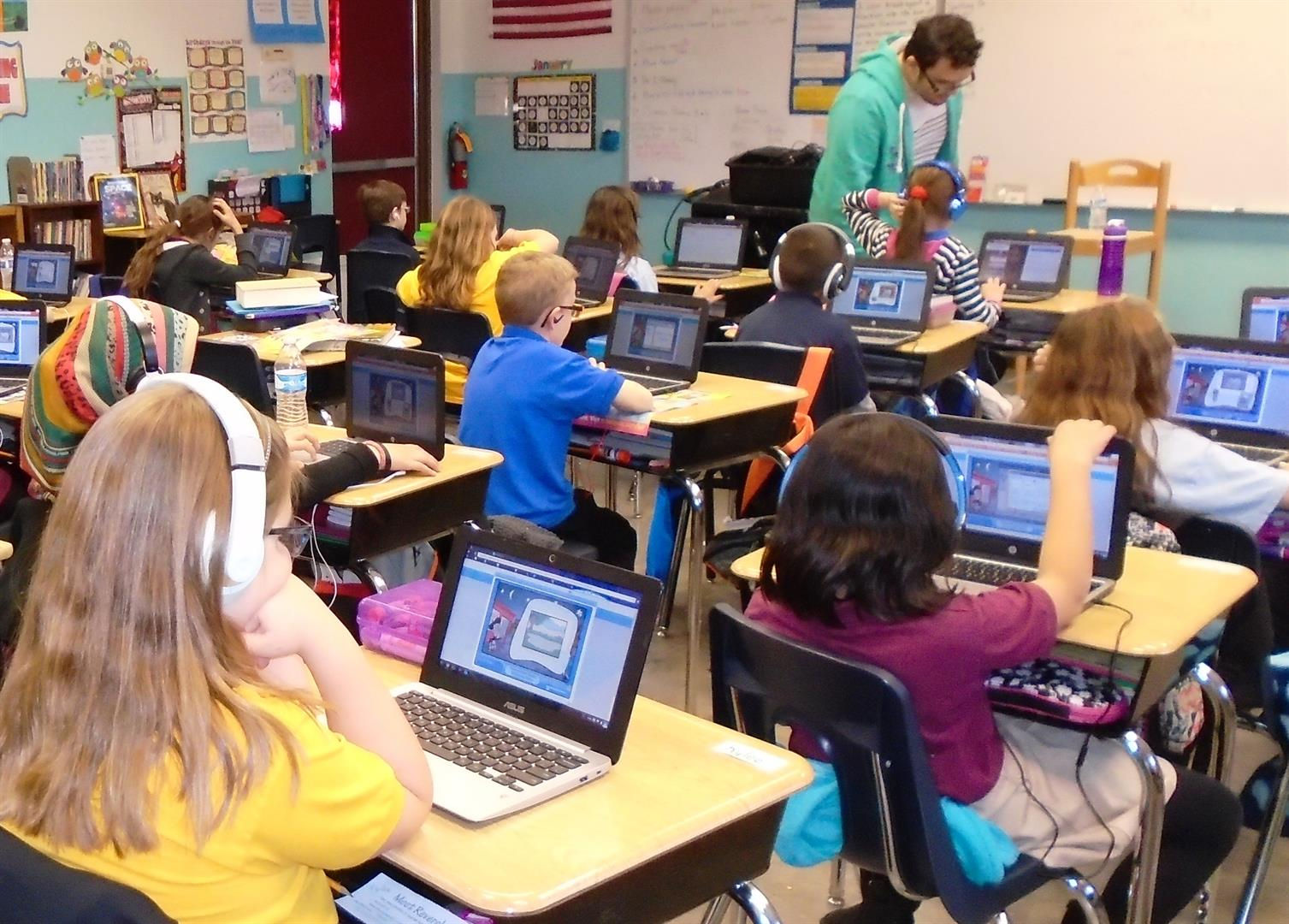 Children in headphones at computers