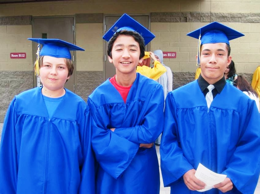 Three boys in cap and gown pose on graduation day.