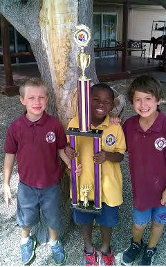 Three boys show off their championship trophy