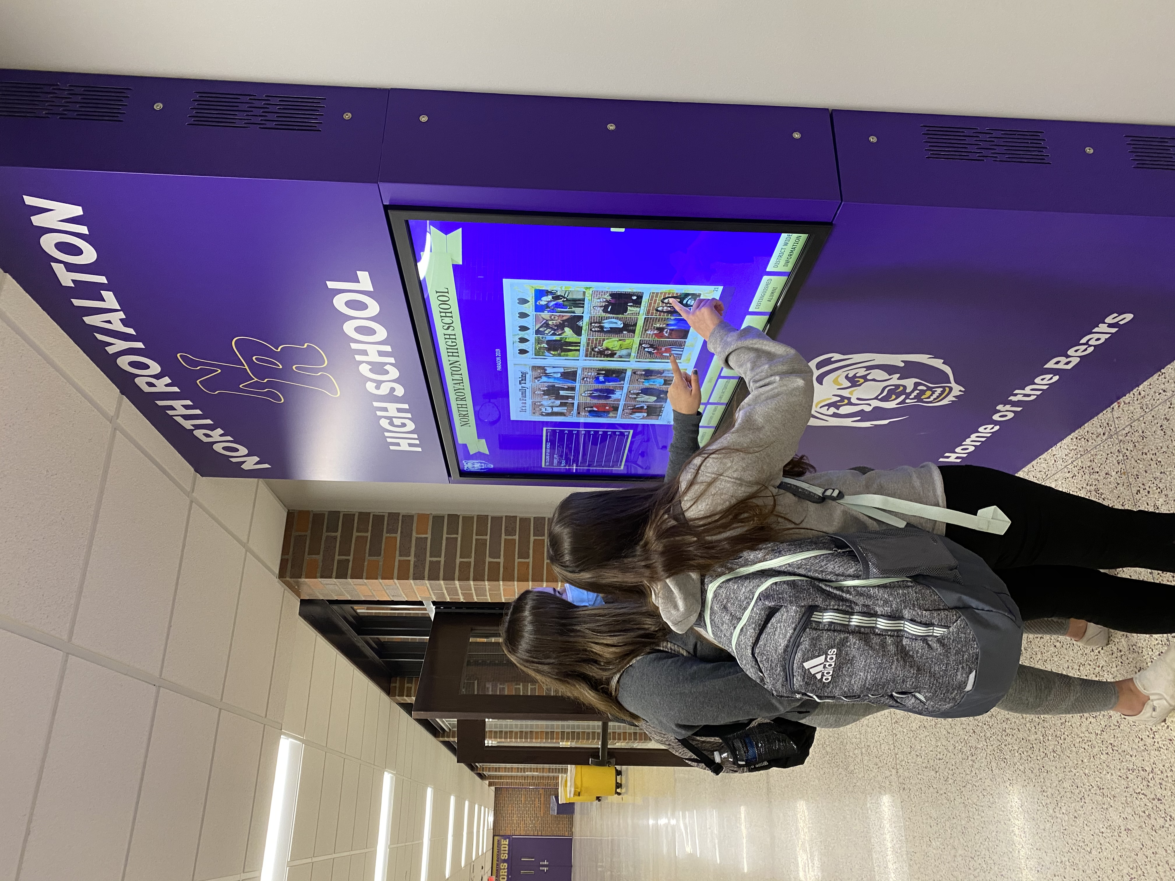 Students enjoying the North Royalton High School electronic kiosk that features class photos, yearbooks, history, distinguished alumni and more, located inside North Royalton High School.